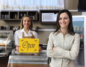 Happy Owner Of A Caf and waitress Showing Open Sign